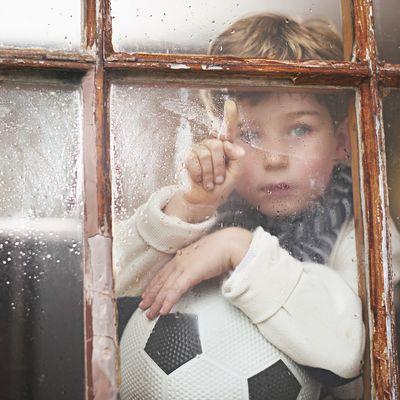 Junge schaut aus dem Fenster