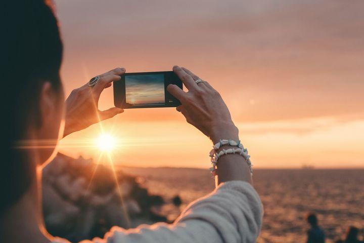 Eine Frau macht ein Foto mit Ihrem Smartphone.