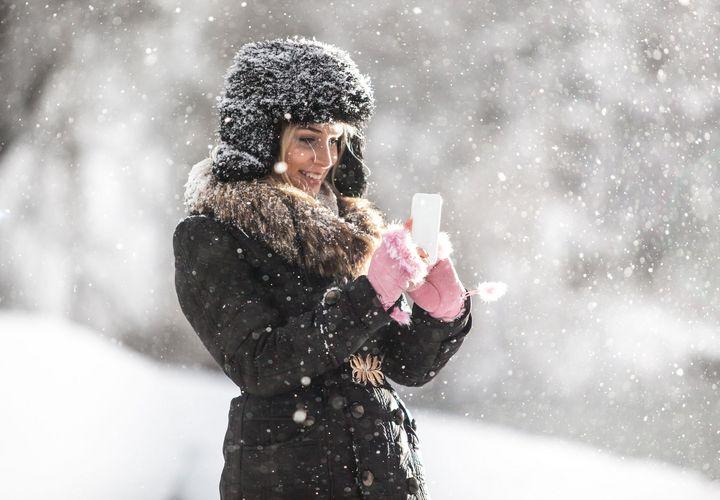 Eine Frau steht im Schnee und bedient Ihr Smartphone