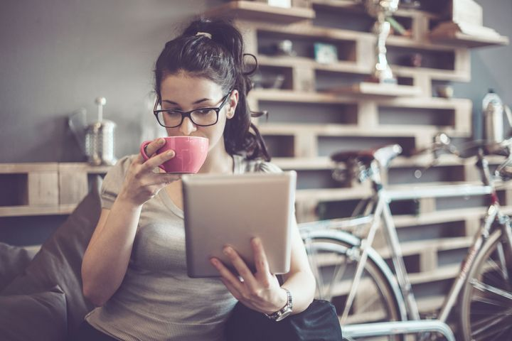 Eine Frau betrachtet Ihr Tablet und trinkt dabei Kaffee