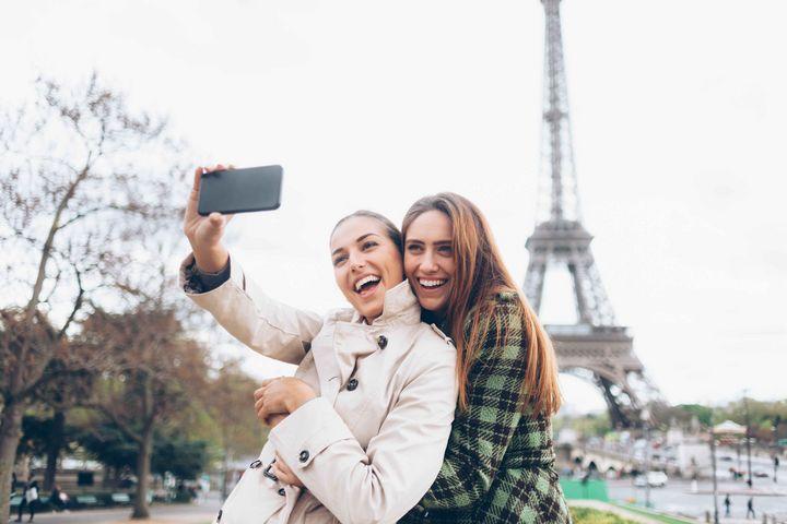 Zwei Frauen fotografieren sich vor dem Eiffelturm