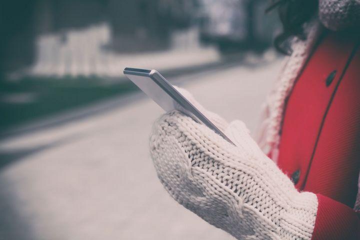 Ein mensch mit dicken Handschuhen bedient sein Smartphone.