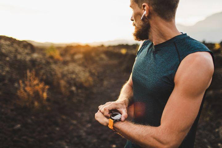 Mann läuft in der Natur mit Kopfhörern und Sportuhr