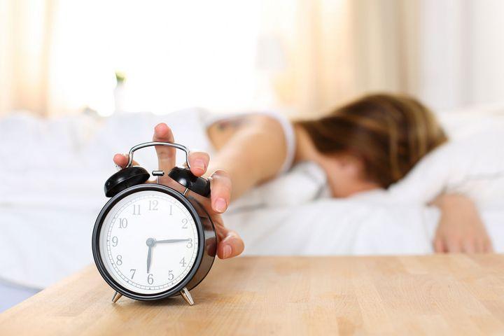 Eine Frau schläft mit Ihrer Hand auf dem Wecker