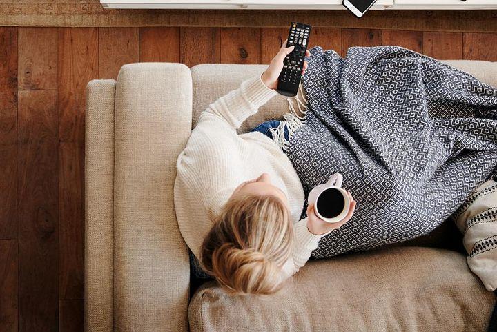Frau mit der Fernbedienung auf der Couch.