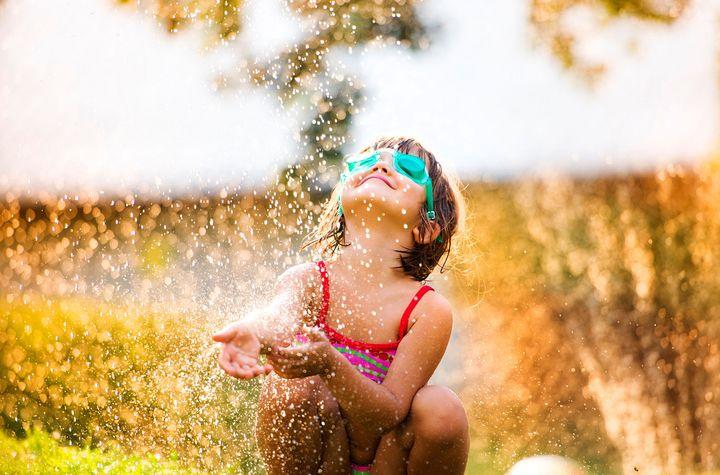 Ein Kind im Regen eines Sprinklers