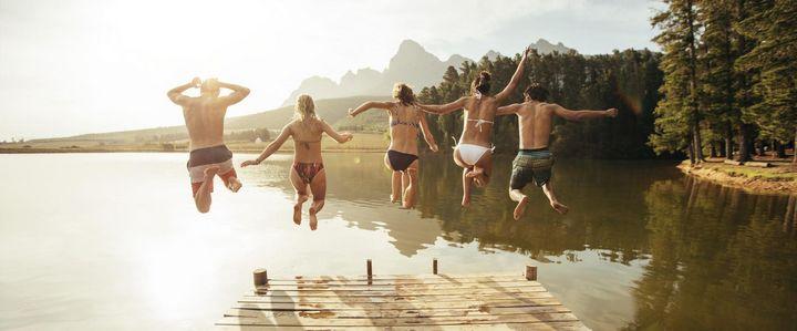 Freunde springen gemeinsam in den See