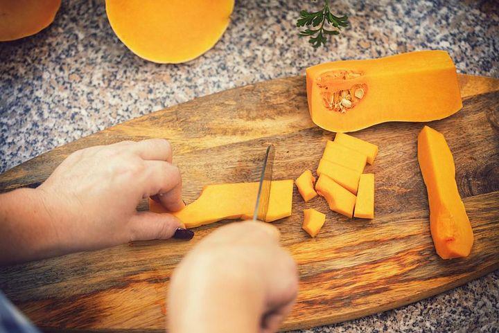 Kürbis für die Suppe schneiden.