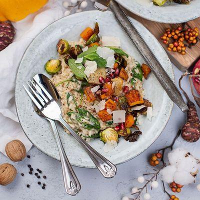 Risotto kann mit Parmesan und Granatapfelkernen garniert werden.
